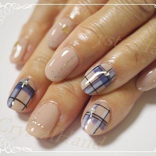 Curiosas uñas en color beige adornadas con diseños de cuadros en negro, azul y azul marino, decoradas con perlas cristalinas y brillos dorados.