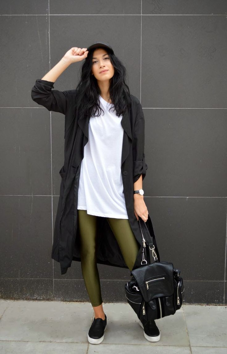 A black trenchcoat and olive leggings feel perfectly suited for weekend activities of all kinds. Black leather slip-on sneakers will contrast beautifully against the rest of the look.  Shop this look for $130:  http://lookastic.com/women/looks/trenchcoat-backpack-slip-on-sneakers-leggings-crew-neck-t-shirt-cap/5446  — Black Trenchcoat  — Black Leather Backpack  — Black Leather Slip-on Sneakers  — Olive Leggings  — White Crew-neck T-shirt  — Black Leather Cap
