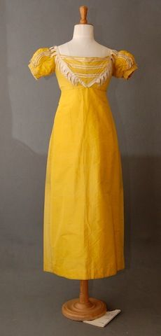Yellow silk dress with cream satin trim, c. 1810. This was almost certainly made from an earlier dress of the 18th C. The front panel of the skirt is a slightly stronger shade than the rest, as is the center back bodice and the puff sleeves. There are fold marks in the skirt front where it has been unpicked.