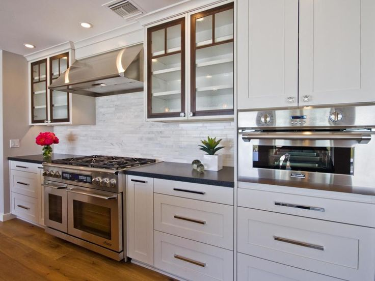 This contemporary kitchen features a fume hood, glass cabinets and tile backsplash.
