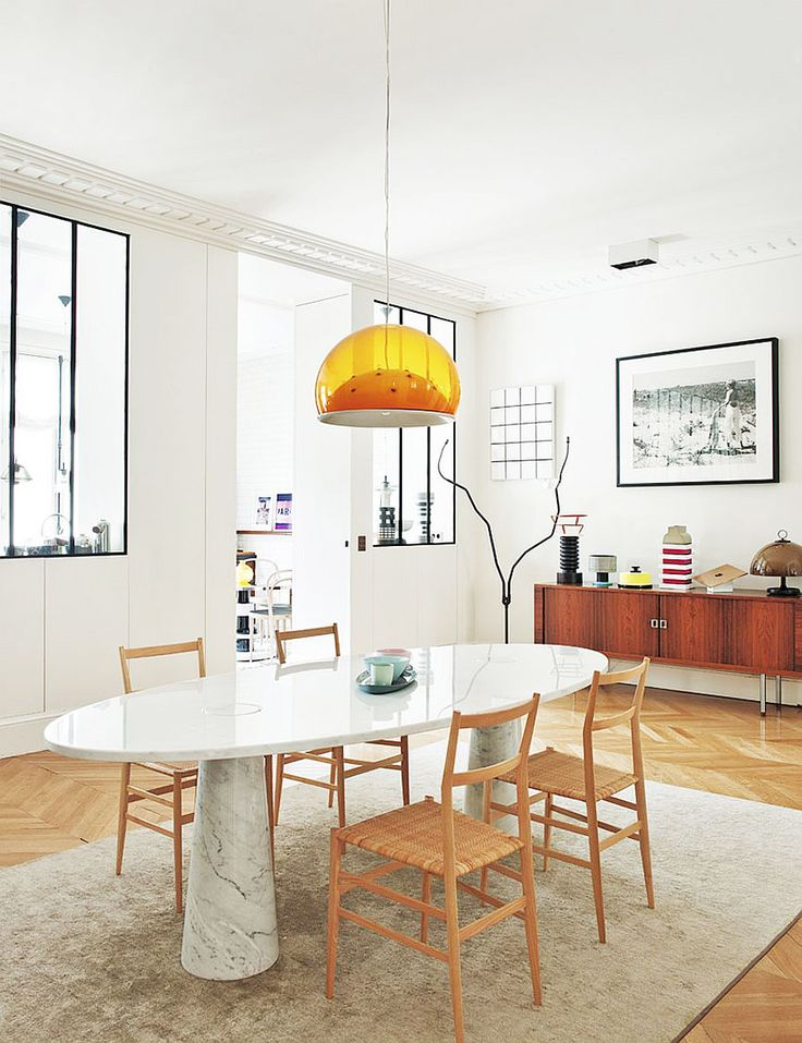 Modern dining space with orange light pendant, midcentury console table, and marble dining table
