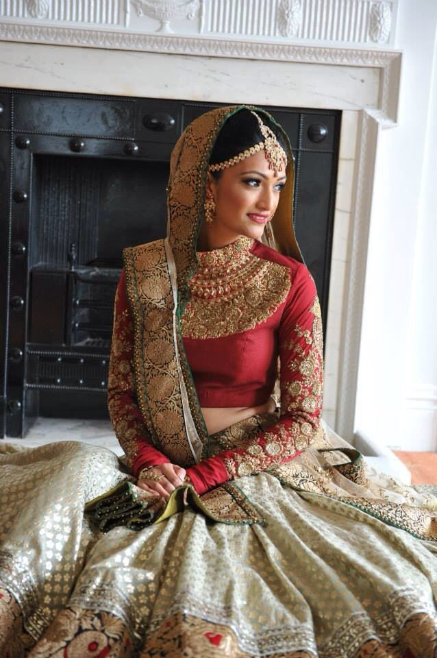 Indian bride in a sabayasachi red and cream lehenga.