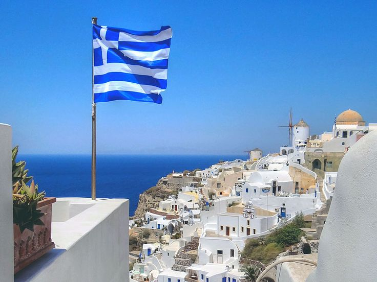 Oia, with Greek flag in foreground. Santorini, Greece.