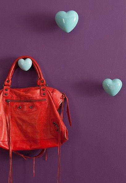 Ganchos em forma de coração vão transformar a parede em um canto charmoso. O contraste de cores deixa a decoração mais alegre. Detalhe do projeto da arquiteta Andrea Murao