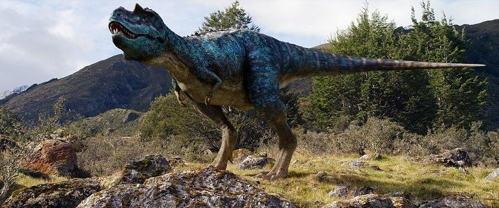 The Gorgosaurus, a bipedal dinosaur depicted with iridescent scales, stands on mostly rocky terrain with deciduous trees behind it.