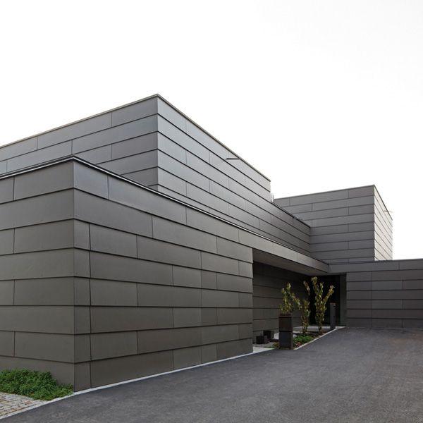 Das elegante Doppelhaus besitzt eine einheitliche Gebäudehülle aus horizontal angeordneten Faserzementtafeln von Eternit.