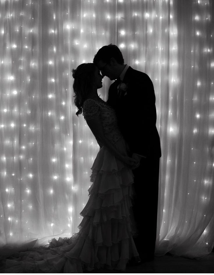 Line the walls of your wedding reception in tulle and string lights. By decorating and illuminating your space you are also hiding what you don't want your guests to see.