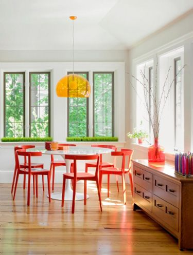 orange chairs, yellow light, airy and bright. I want to sit in this room.