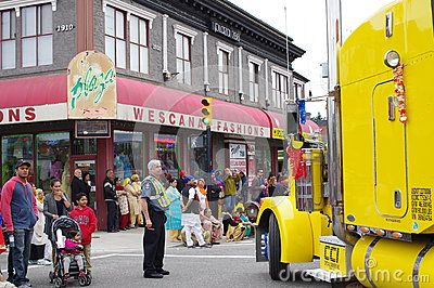 Parade truck making a turn from Main Street to 49th Ave, Vancouver's Punjabi district, with policeman regulating safety. Picture taken on: April 16th, 2016