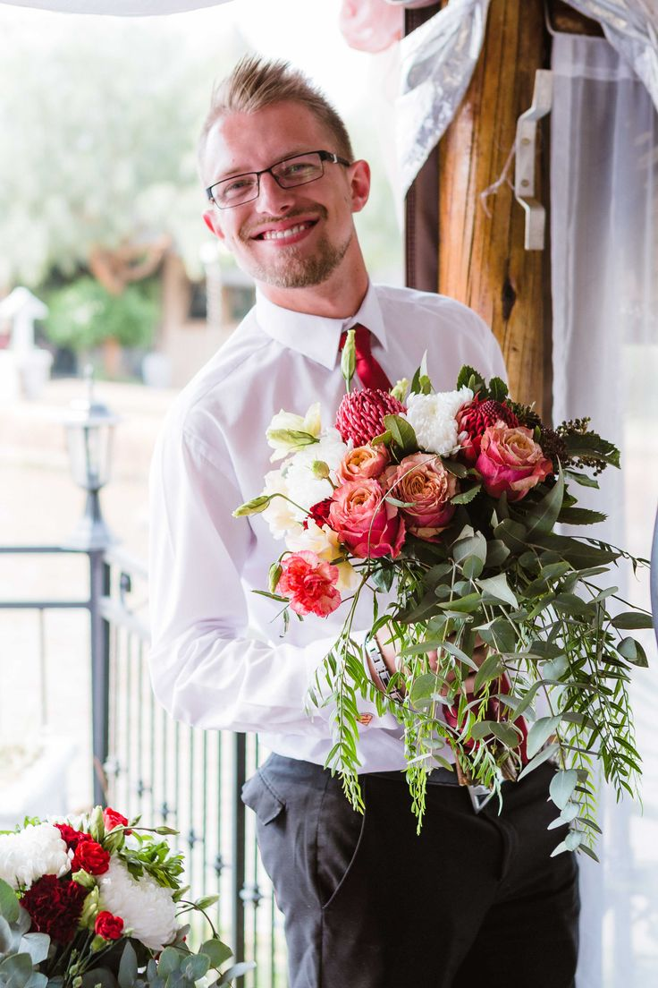 Free-form Bridal Bouquet by Pronkertjie {Gauteng, SA}. We love this photo so much - Best Man holding the Bridal Bouquet = Priceless! The bouquet includes Red Waratahs / Telopea's, Peach / Blush Lisianthus, Burgundy Carnations, Snowdon White Chrysanthenums, Crystal Leila Carnation and a combination of Pennygum, Pepper Tree Leaves & Viburnum. {Full album available at www.pronkertjie.co.za}