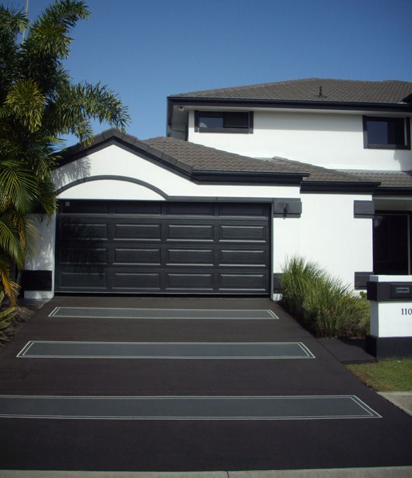Concrete driveway black and grey matching white house with for Black roof house