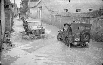 Jeeps passant dans le village inondé de Bretteville - L'Orgueilleuse, le 21 Juillet 1944.