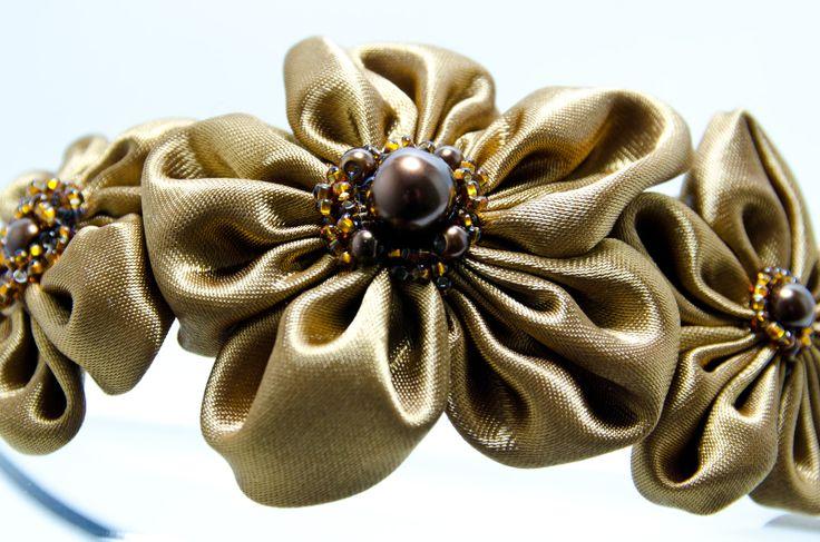 Čelenka Rozalia zlatá Kovová čelenka o šířce 0,5cm,barva černá. 3ručně šitéh saténové květinky ve zlaté barvě. Středy květů jsou vyšity rokajlem a perličkami. Velikost květů jsou2 x 3 - 4 cm a 1 x 7 cm.Celková délka aplikace cc 11-15cm. Pro pohodlnější nošení jsou květy podlepeny filcem. Foto: Michaela Nohejlová-Neofoto Jedná se o autorskou čelenku. Jedná ...