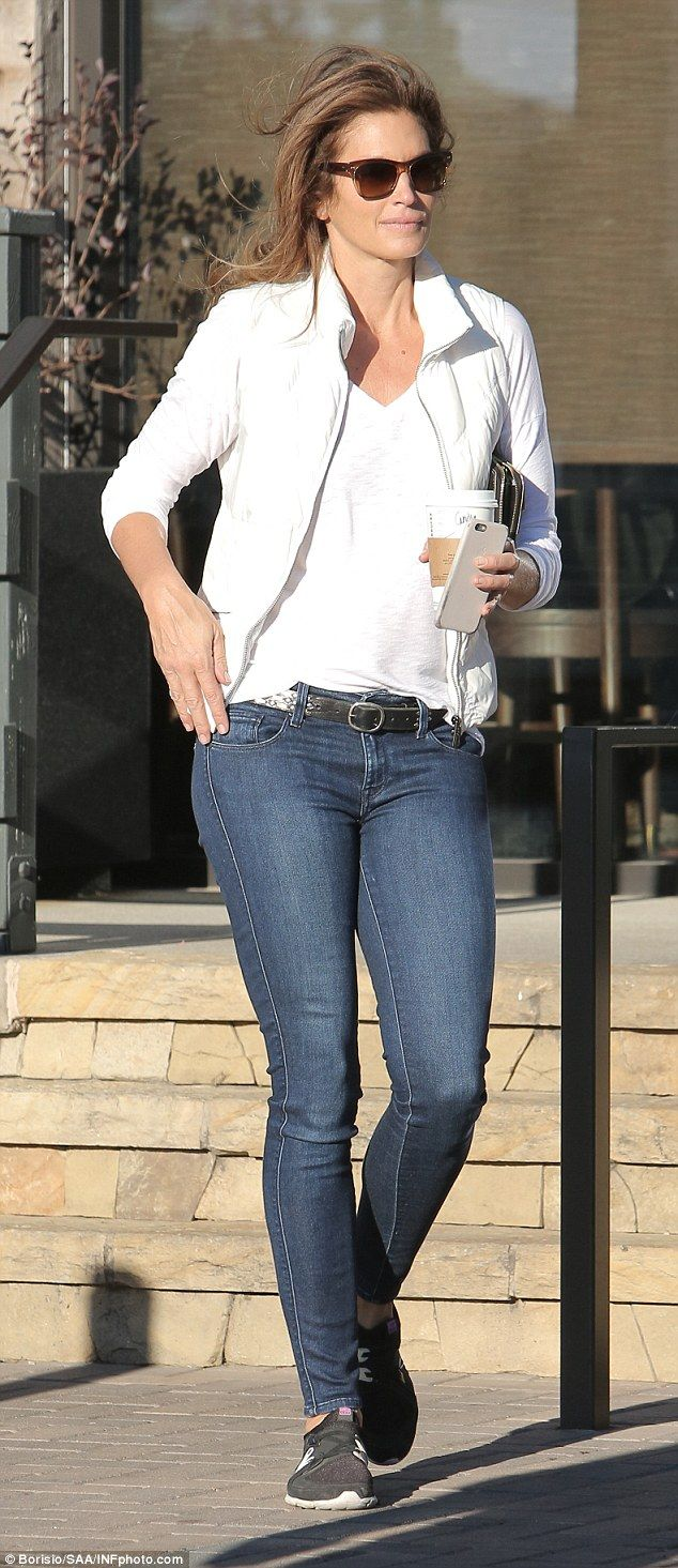 Cindy Crawford leaves Starbucks in Malibu in jeans and a white T-shirt with a cup of coffee in her hand