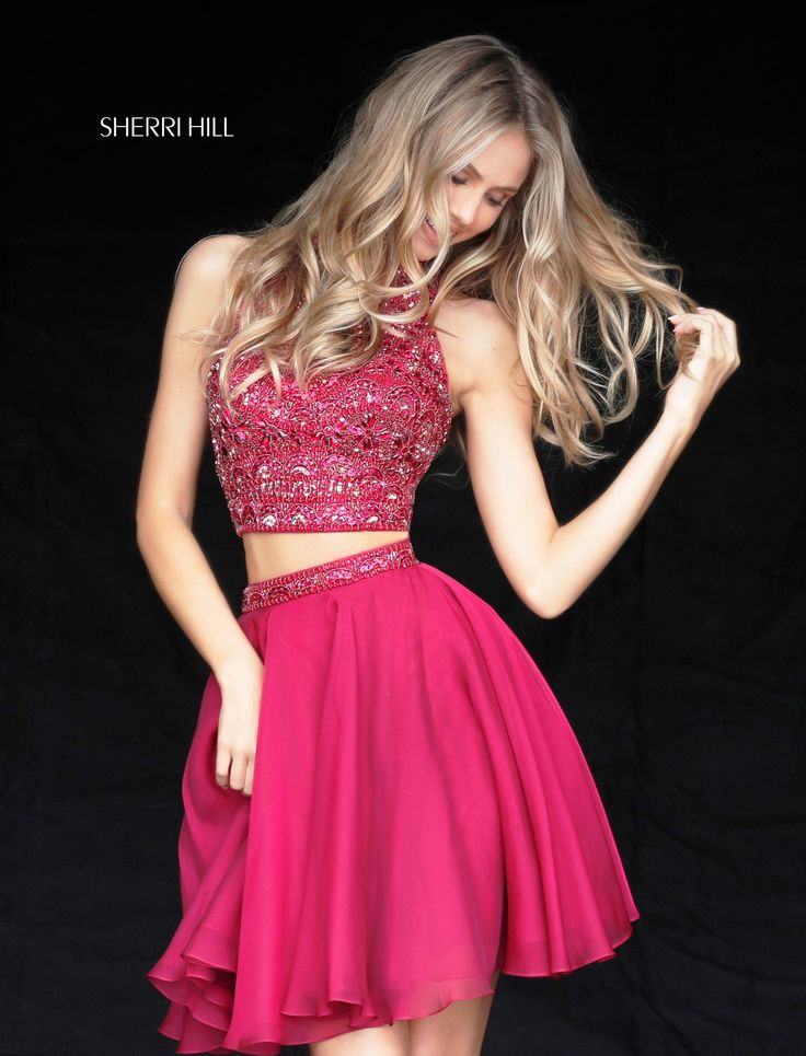 It takes two in Sherri Hill 51296. This fun and flirty two-piece features a dazzling jeweled top with a high neckline, and open triangular back, with hook closure. The short A-line chiffon skirt has a jeweled waistband. Shimmer under the spotlight when you wear this look for a Sweet 16, wedding, or homecoming dance.  var _currentScript = document.currentScript || null; (function () { var script = document.createElement('script'); script.type = 'text/javascript'; script.src…