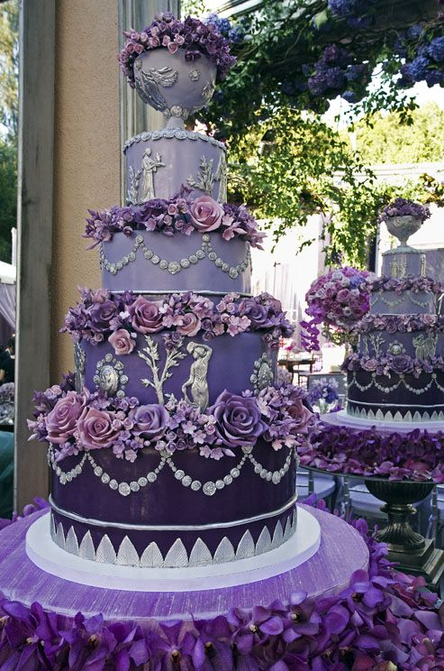 This ornate #wedding cake, in shades of purple and silver, features hand-made sugar roses and silver fondant Grecian figures.