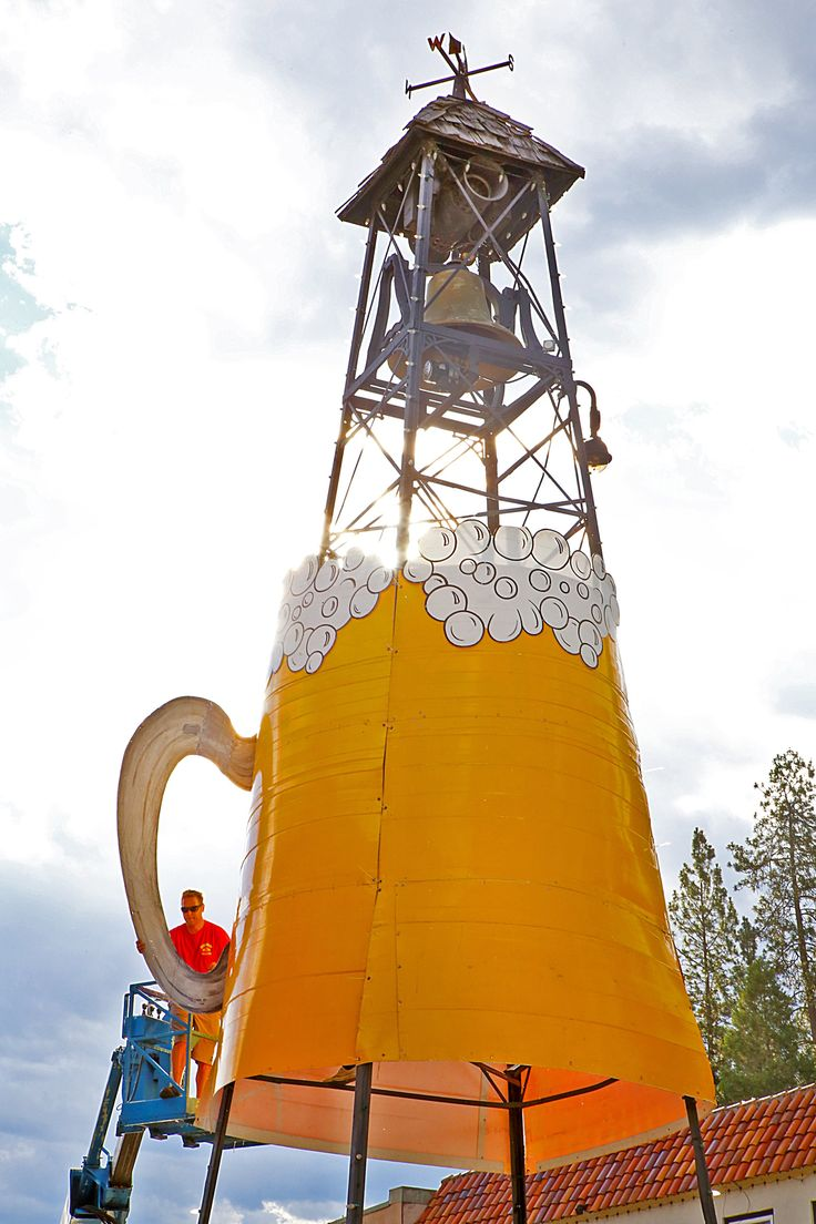 Dave Rudolph, co-owner of Eco Signs, holds the handle of the giant beer mug as Joe Lucier (inside the mug) attaches the handle with zip ties on the frame of the Bell Tower. The stein signals that the Placerville Bell Tower Brewfest is happening on Main Street in Placerville on Saturday, June 24...  #mountaindemocrat #Prospecting #B1, #Printed