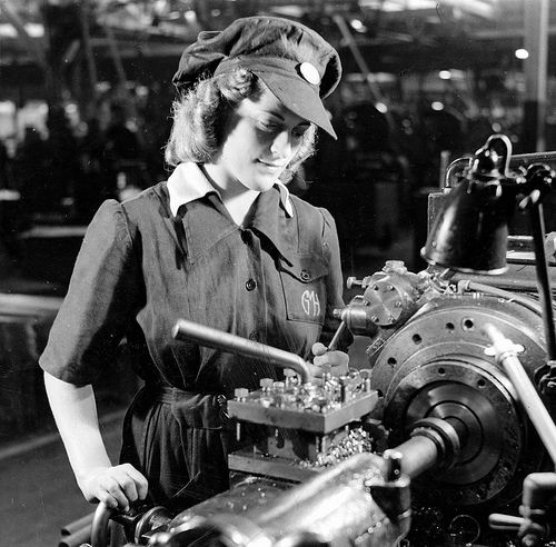 A young woman cutting driving bands for anti-aircraft shells in a munitions factory in South Australia in 1942. Photographer: Smith, D. Darian