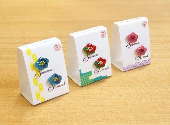"""【各種イヤリング部品への交換対応商品】日本の伝統的な吉祥文様をポップ・モダンにアレンジしてピアスにするシリーズで、今回は1弾目として梅をモチーフにしています。 表はレジンでぷっくり加工、 裏はパールホワイトのマニキュアコーティング仕様です。 バリエーションは桃×紫、緑×赤、青×黄の3種類です。 ご注文時にご希望の種類を承ります。梅は春1番に咲く花なことから昔から縁起の良い柄とされてきているのですが、 パッケージにはこのように梅が吉祥文様とされた由来を簡単な英語で記しています。 また、英語・日本語の両方で""""吉祥文様「梅」""""というタイトルが入っています。日本人の方にも日本人以外の方にも、 日本文化に触れて理解するちょっとしたきっかけとなるよう、 ピアス単体だけでなくパッケージまで含めて1つの作品としてまとめました。『春のおでかけハンドメイド2016』■サイズ…ピアス/縦約12×横約15mm、パッケージ/横38×高さ51×奥行き30mm ■素材…ピアス/透明樹脂・サージカル・真鍮・プラ版、パッケージ/フォト半光沢紙(絹目)【在庫】…"""
