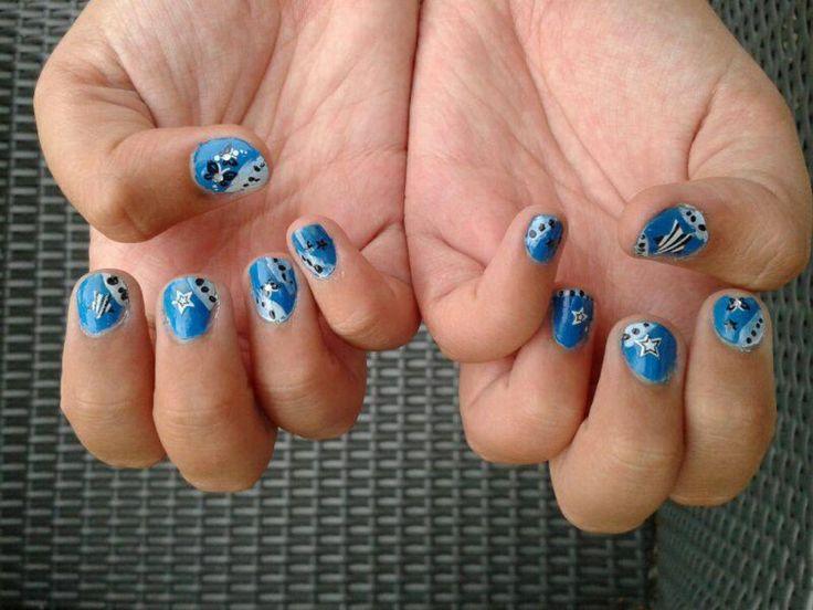 Zelf gemaakte blauwe nagels met stikkers, streepjes en stippen