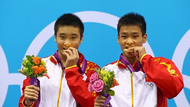 Yuan Cao and Yanquan Zhang of China celebrate with their gold medals during the medal cermony for the men's Synchronised 10m Platform Diving on Day 3 of the London 2012 Olympic Games at the Aquatics Centre