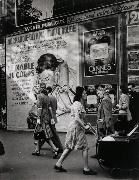 """Brassaï - Passants devant l'affiche du film """"Le diable au corps"""", Les Grands Boulevards, Paris, vers 1947."""