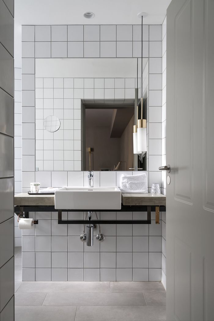 A white tile bathroom with hanging, modern light fixtures and light gray tile flooring.