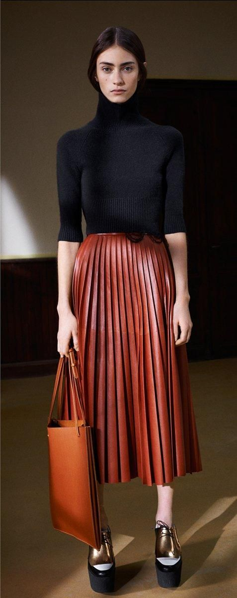 The fall uniform: Burnt orange pleated skirts, orange leather bags and black turtlenecks at Céline