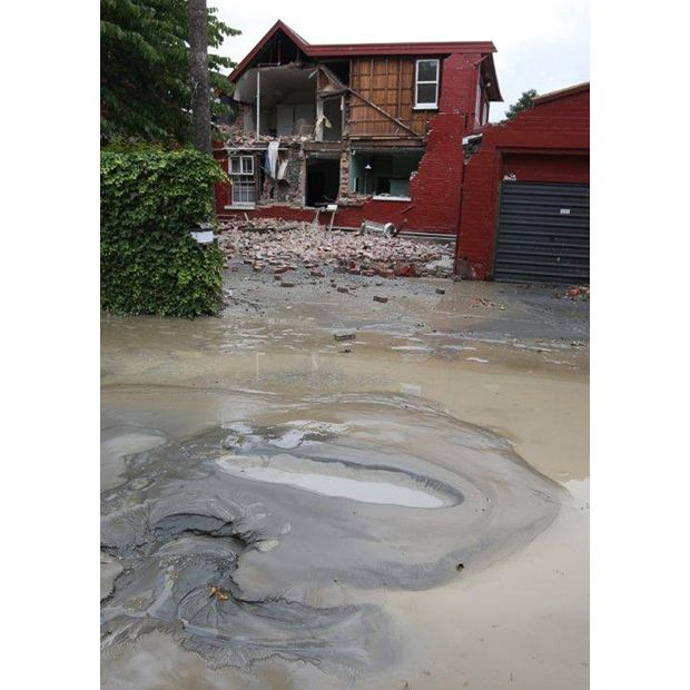 Liquification bubbles to the surface in front of a damaged house in Christchurch, New Zealand after the earthquake