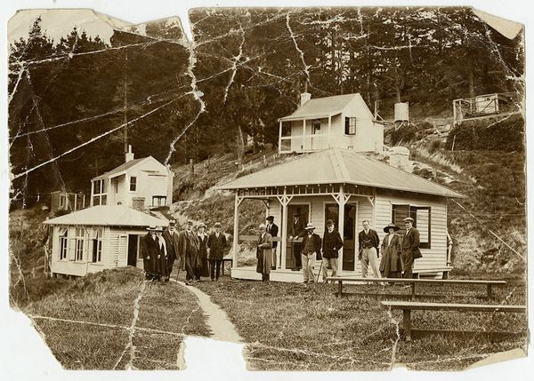Leper Huts and health officials on Quail Island.Photo shows Dr Charles Upham of Lyttelton, Port Health Officer in panama hat, centre, Jack Annan (Assistant Health Officer and the Health Department's Lyttelton Disinfecting Officer) and his wife Annie. The leper colony on Quail Island was closed in 1931 after Jack Annan was injured when a pole fell on him while dismantling the huts and was dead on arrival at Christchurch Hospital.