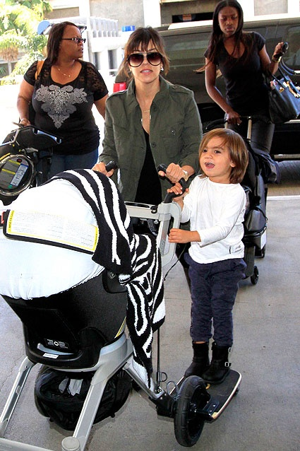 Mason Disick hitched a ride on his sister's stroller as he, his mom Kourtney Kardashian and baby Penelope Disick boarded a flight out of LAX on April 19, 2013. Dad Scott Disick was also in tow.