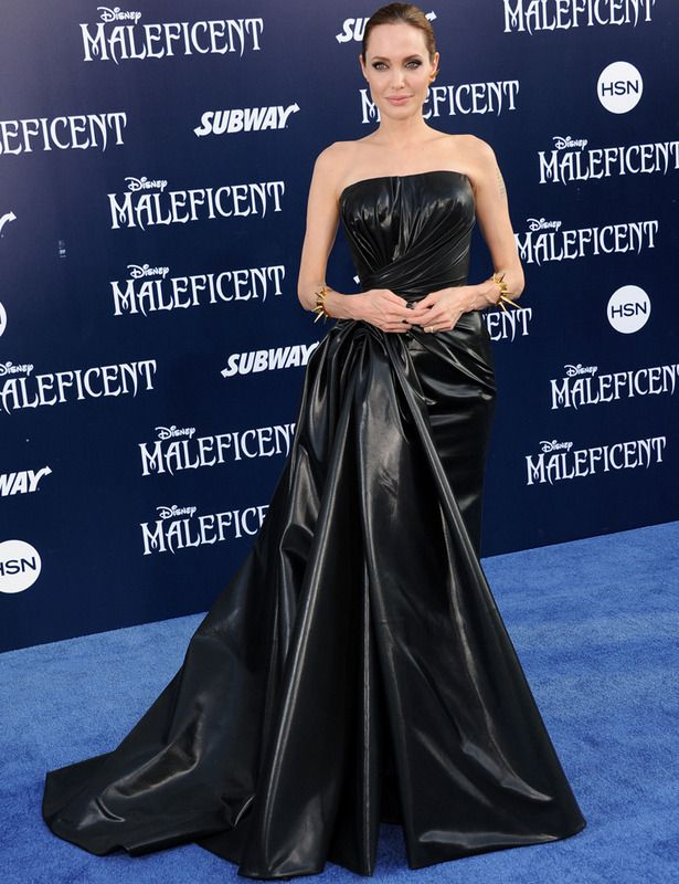 En Los Angeles Angelina Jolie se metió en papel de Maléfica durante la premiere de la película de la manera más sofisticada con este vestido negro de escote palabra de honor y voluminosa cola, obra de Atelier Versace. Lo combinó con unos llamativos brazaletes dorados con pinchos y recogió su melena en un moño tirante.