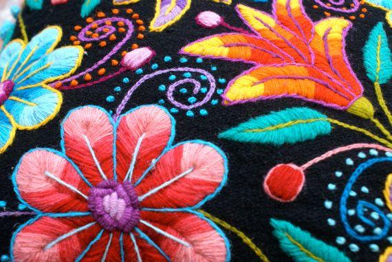Flores de colorido vibrante, pop muy bien desde el fondo negro de este cojín bordado mano. Texturas fantásticas de costura desde los Andes a su hogar. El pilllows primer tejidos en telar tradicional con lana de oveja y más adelante adornados con bordado de flores hechas de lana de alpaca a mano. Un juguetón crochet adorno da este cojines el acabado perfecto.  Cierre de cremallera trasera. Medidas 16 x 16 en  1 fundas incluidas. Partes movibles ni rellenos incluidos  Tenga en cuenta que las…