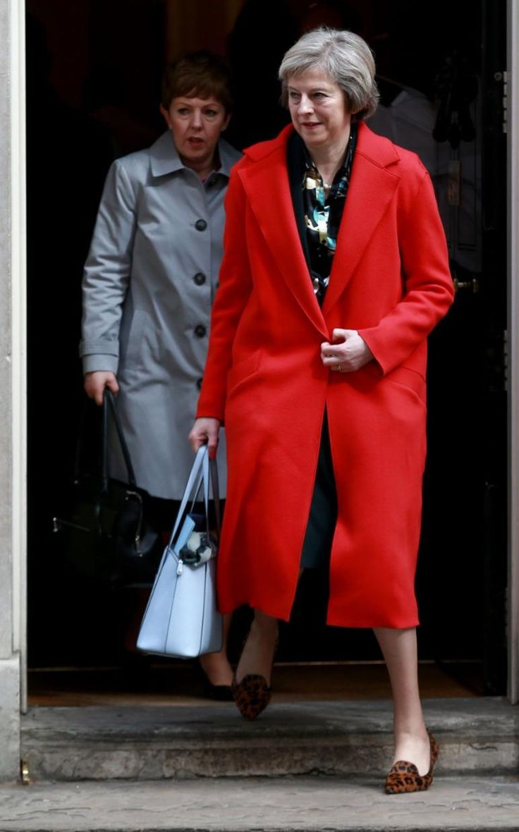 Theresa May wears a pillabox red coat with her LK Bennett blue bag and LK…