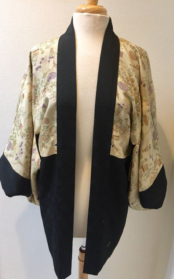 Beautiful Black & Ecru / Reversible Asian Art Deco / Floral / Chinese Short Kimono / Haori Short Robe / Smoking Jacket, all Hand Made  Gorgeous Hand made reversible Haori short robe features 2 sides, one is black with fine Chinese Motif pattern that has silver and copper squares painted on here and there, and the other side is Ecru in color and has an Asian floral pattern with square, oblong, and fan shapes. The colors are burnt red, purple, green and beige. All H...