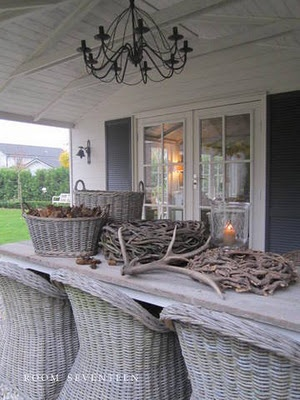 love the washed out feel of the wood and wicker, great chairs! great covered porch!