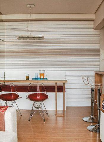 A mesa de jantar (1,70 x 0,75 x 0,70 m) é destacada por uma luminária de vidro e aço, com quatro lâmpadas halógenas PAR 20. Lustres Iriê, R$ 190. Usar papel de parede foi uma saída interessante para mexer na decoração de forma clean. O modelo listrado (Wallpaper) utilizado na sala alonga visualmente o espaço. As peças somam estrutura de inox e assento de acrílico transparente. Da Sun House, R$ 510 (cadeira) e R$ 397 (banqueta).