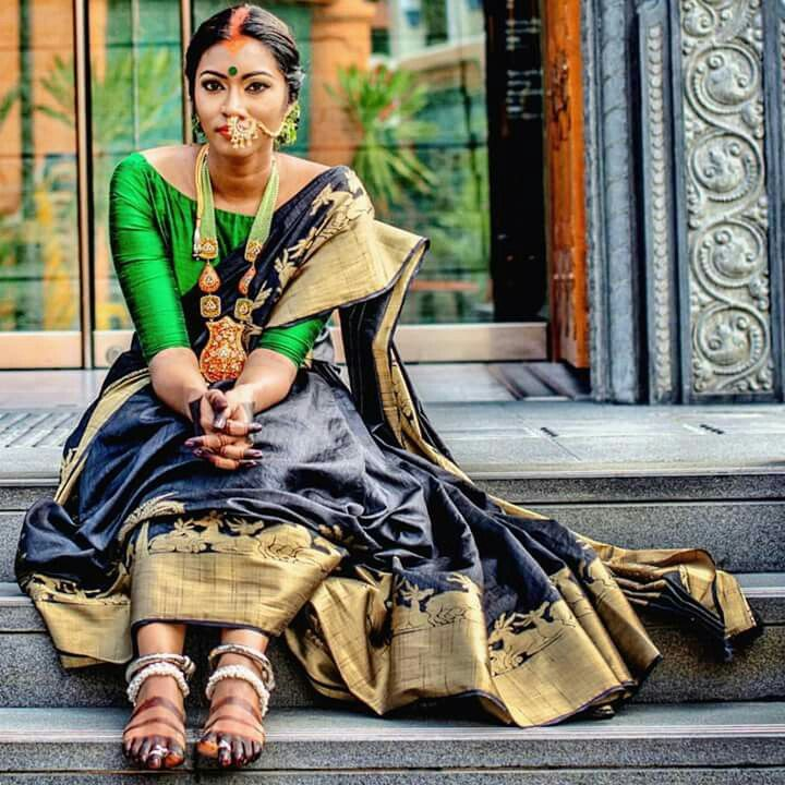Black and gold silk saree with green long sleeve boat neck silk blouse