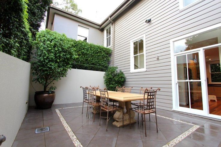 Courtyard. House painted in Dulux Crust with Antique White USA trim and accents of Jasper. Walls painted in a really versatile colour Self Destruct. Table and chairs from Yard Ware, Sydney Grey tile with pebble boarder. This is our old house in Hunters Hill, a Sydney, Australia that we loved very much. Whilst this photo was taken on a rainy day, this was a fantastic sun trap.