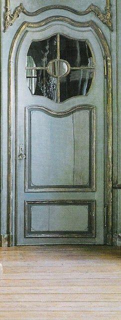 Blue gray French door, accented in gold (Design: Axel Vervoordt)