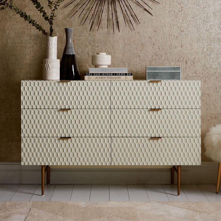 With its geometric, textured drawer fronts and smooth lacquer finish, our retro-inspired Audrey Chest of Drawers makes quite an impression. Slim, antique brass-finished metal drawer handles pull the look together.