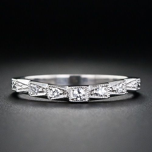 This is a perfect wedding band for Art Deco or vintage diamond engagement rings. The slightly contoured band features five round diamonds set in geometric settings which are finished with milgrain details.