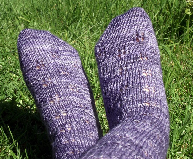 Lilac Petals by Abbey Morris. The lilac flower pattern alternates around the leg, down the instep and ending just before the toe. There is an option to have a single lace lilac flower on the heel or just a plain stockinette heel.  With these socks you can have lilacs all year round.