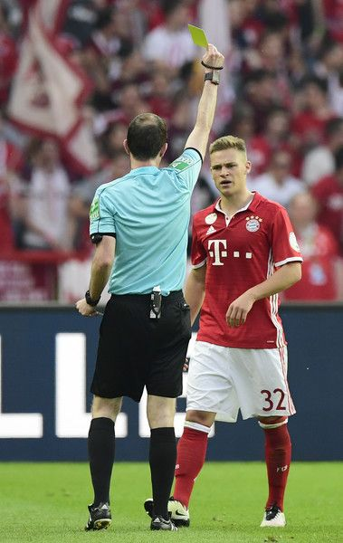 Referee Marco Fritz (L) shows the yellow card to Bayern Munich's midfielder Joshua Kimmich during the German Cup (DFB Pokal) final football match Bayern Munich vs Borussia Dortmund at the Olympic stadium in Berlin on May 21, 2016.