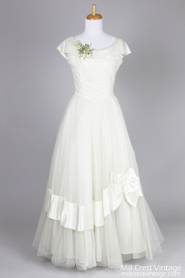 Designed in the 50's, this gorgeous vintage wedding gown is done in a ivory toned tulle over a layer of net and is lined in taffeta. The bodice offers a sco...