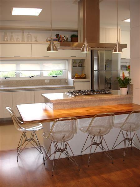 A cozinha deste apartamento localizado em São Paulo, tem aproximadamente 20 m². A bancada de teca foi fixada na alvenaria do balcão de granito que também abriga o cooktop. Três pendentes cromados iluminam a área de refeição. Projeto de Anna Maria Parisi.