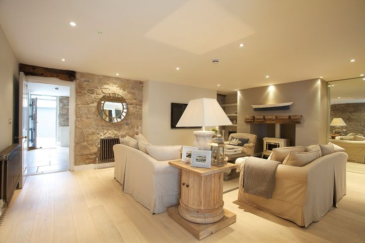 gorgeous pale chalky neutral living room with recessed spot lighting and white wood burning stove
