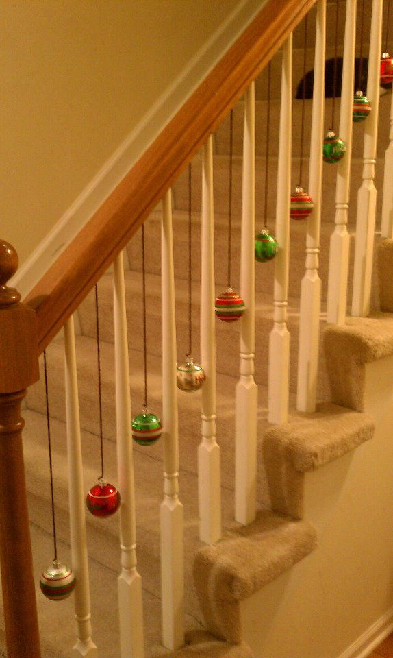 I tied yarn to the ornaments and taped them under the handle.  This way if my kiddies pull them down, there won't  be any damage to the banister and my little ones won't get hurt by sharp tacs.