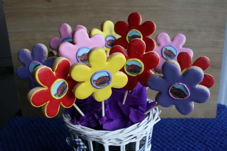 colorfull flower cookies with frosting print in center of the flower.