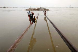 Villagers use part of a damaged railway track to cross floodwaters in Sultan Kot, Sindh province after torrential monsoon rains triggered Pakistan's worst natural disaster on record in 2010
